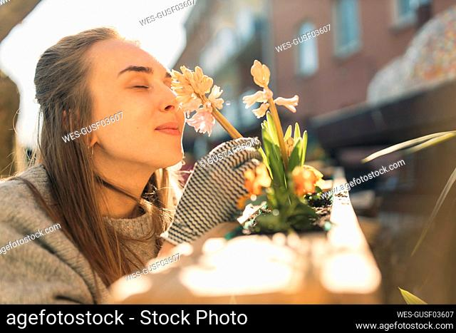 Young woman smelling at flower in garden