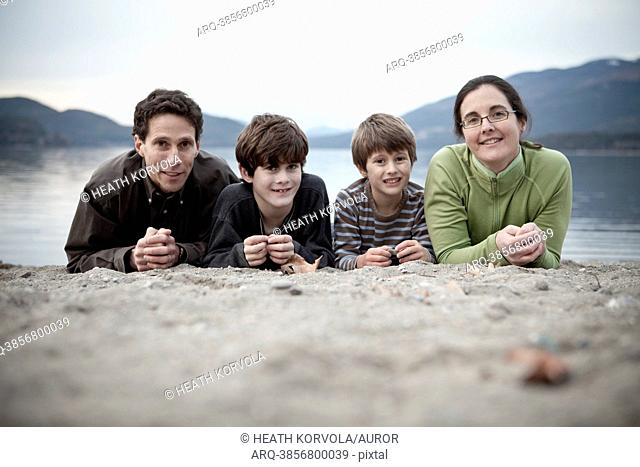 A family takes a portrait on the beach of an alpine lake