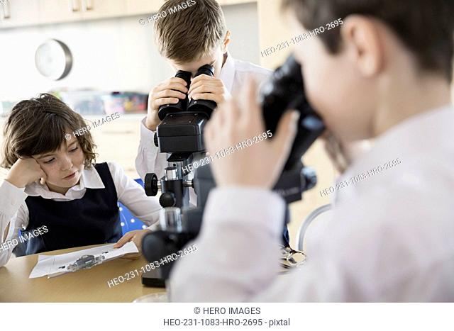 Elementary students using microscopes in science classroom