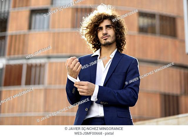 Portrait of young fashionable businessman with curly hair wearing blue suit buttoning cuff link