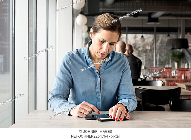 Woman in cafe using cell phone