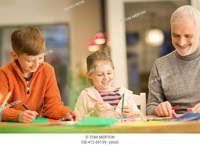 Father and children bonding, doing crafts at table