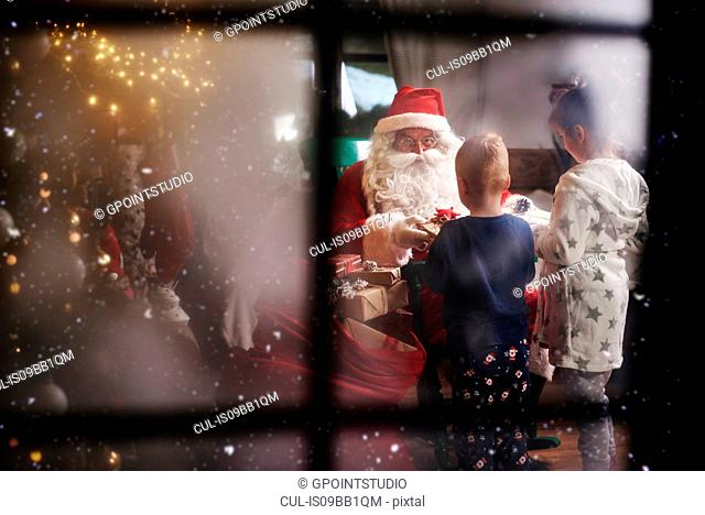 Young girl and boy receiving gifts from Santa, viewed through window