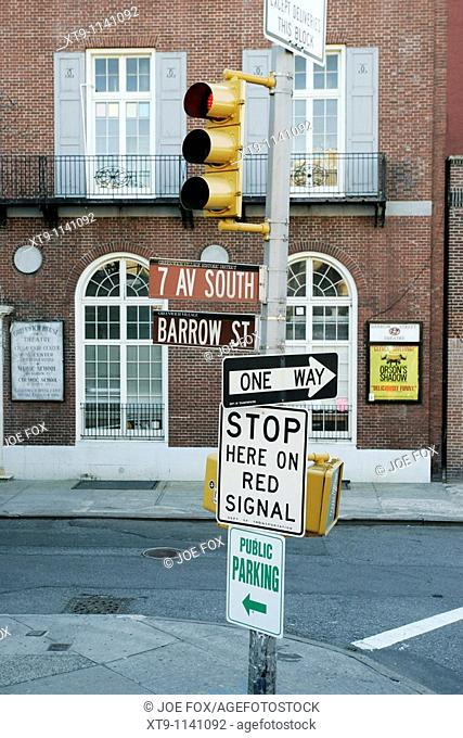 traffic lights and collection of street signs 7th Ave South Barrow Street One Way Stop here on red signal public parking greenwich village new york city