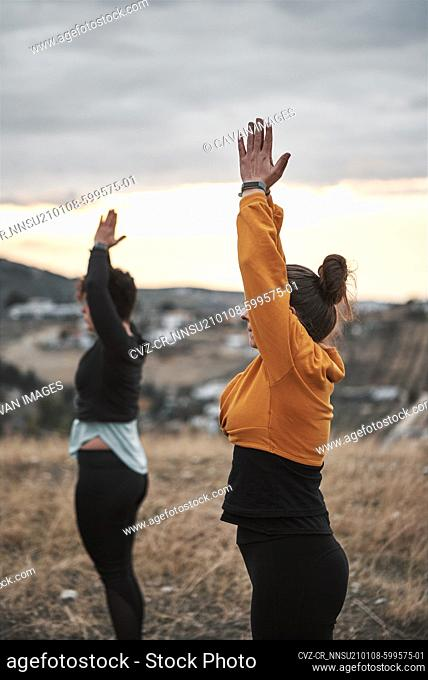 2 young women practicing pilates in the countryside