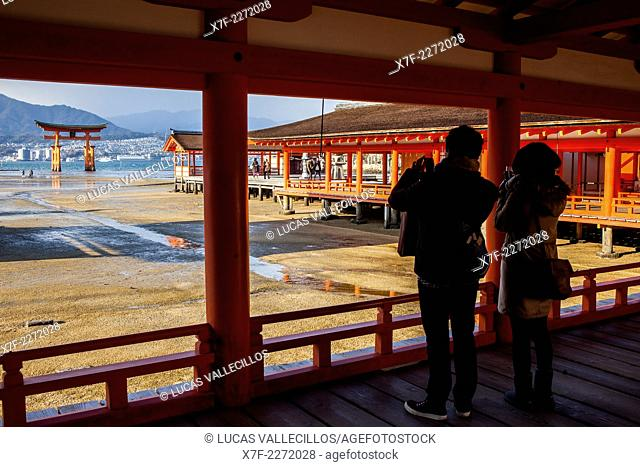 Visitors,Itsukushima Shinto Shrine complex, in background O torii Gate, the giant torii gate that is part of the Itsukushima Shinto Shrine complex