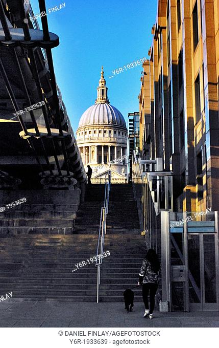 View of St. Paul's Cathedral from the banks of the River Thames by the Millenium Bridge (seen on the left-hand side) including street vendor on Peter's Hill and...