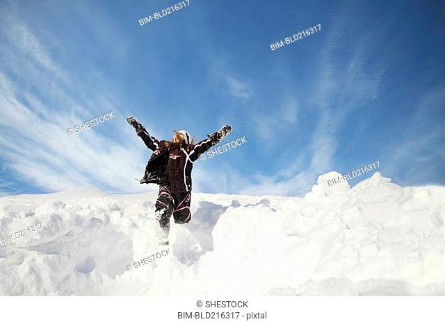 Caucasian girl jumping on snowy hillside