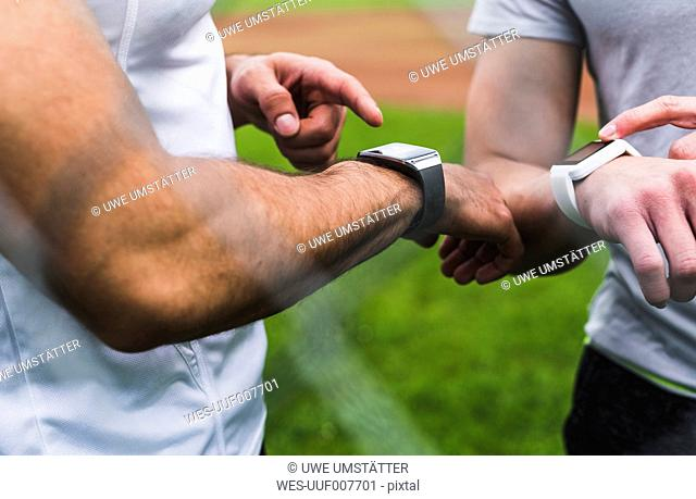 Close-up of two athletes with smartwatches outdoors