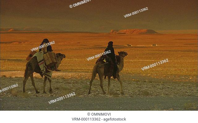 Two Arabic males riding Camels in desert landscape with mountains in distance