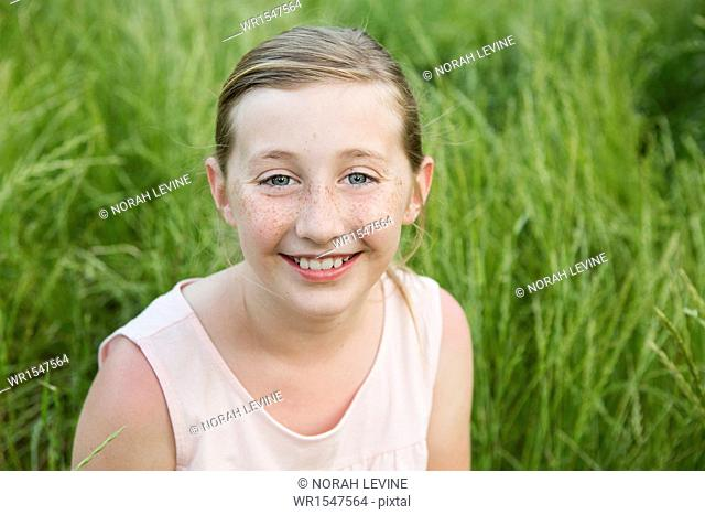 A young girl smiling, sitting on the ground