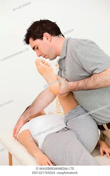 Woman lying while a physio moving her leg in a room