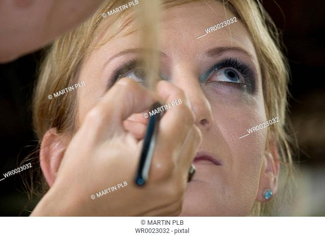 young woman gets make-up from make-up artist