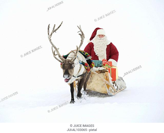 A reindeer pulling Santa Claus and his sleigh of presents