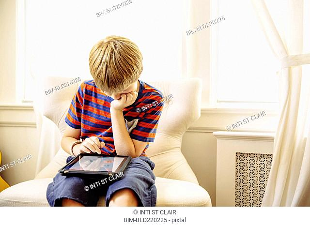 Caucasian boy using digital tablet in living room