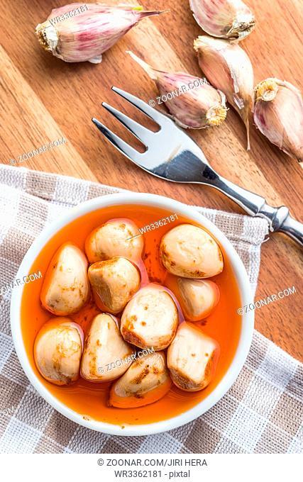 Tasty preserved garlic in bowl