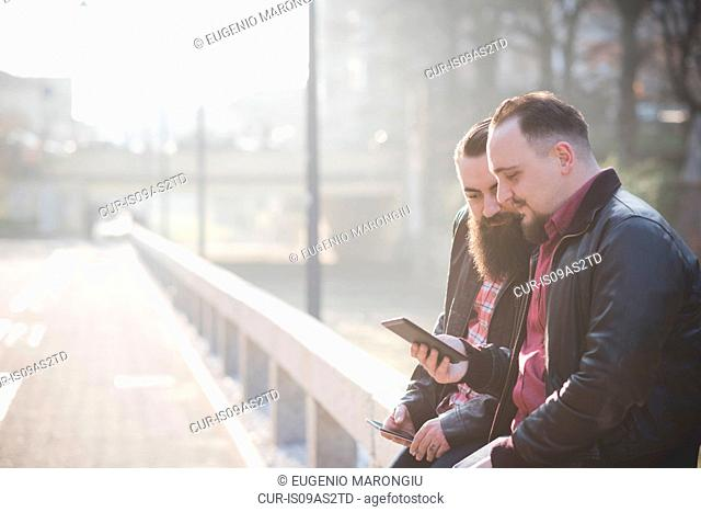Gay couple using smartphone on pavement