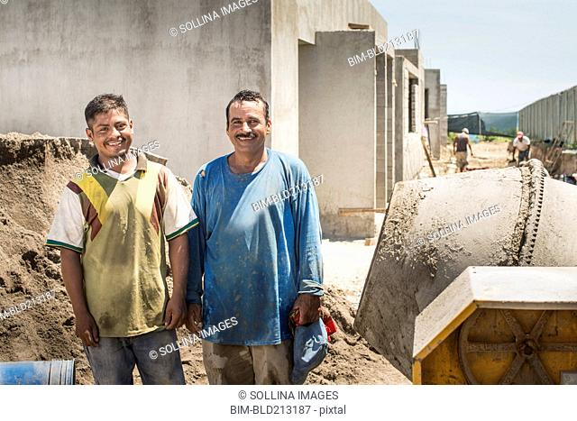 Hispanic construction workers smiling at construction site