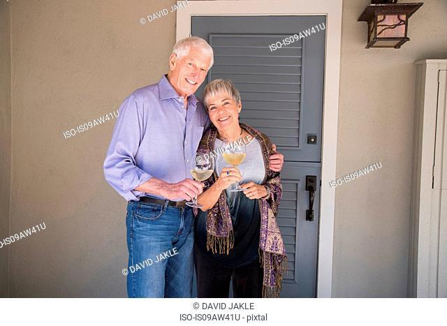 Portrait of senior couple, holding glass of wine, smiling