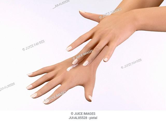 Studio shot of woman applying moisturizer to hand