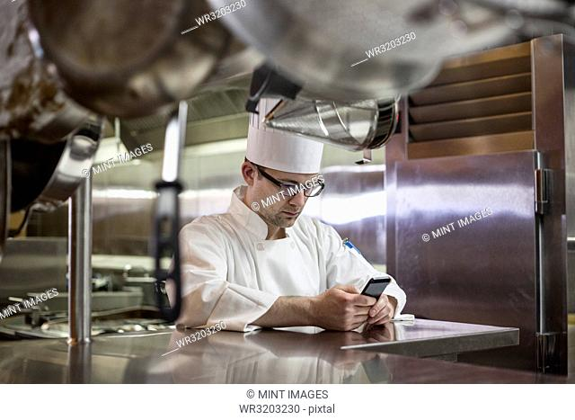 A Caucasian male chef checking his cell phone in a commercial kitchen