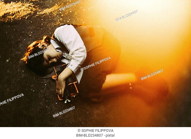 Old-fashioned Caucasian boy laying in street holding machinery