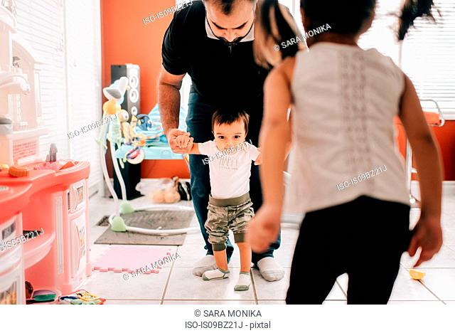 Girl in front of father walking baby brother in kitchen