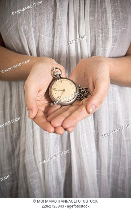Close up of a woman's hands holding vintage pocket watch