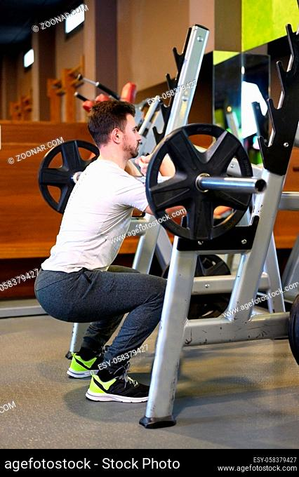 Fit Woman Squats With Barbell Back In Front Of Mirror Inside Gym. High quality photo