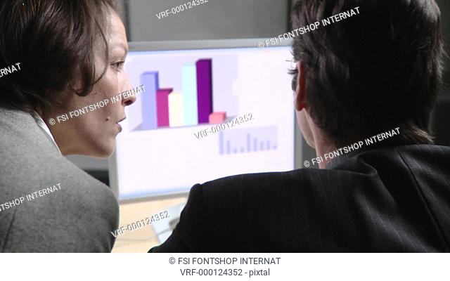 Rear view of businessman and businesswoman reviewing graph chart of computer monitor