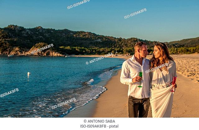 Young couple strolling with champagne on beach, Castiadas, Sardinia, Italy