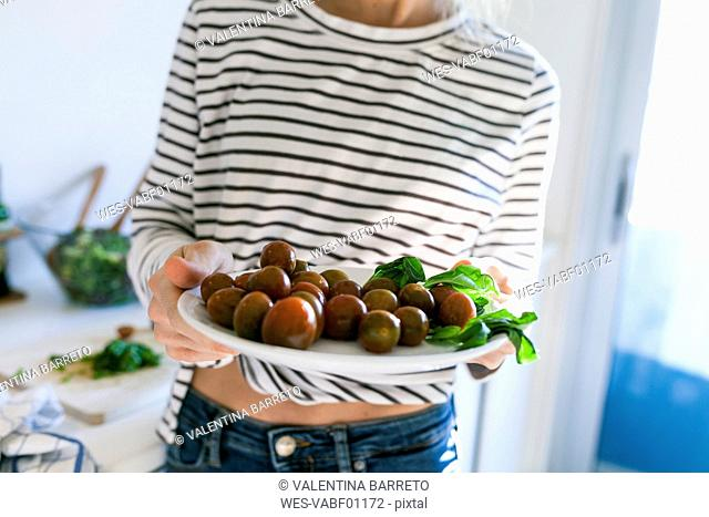 Young woman holding plate of cherry tomatoes