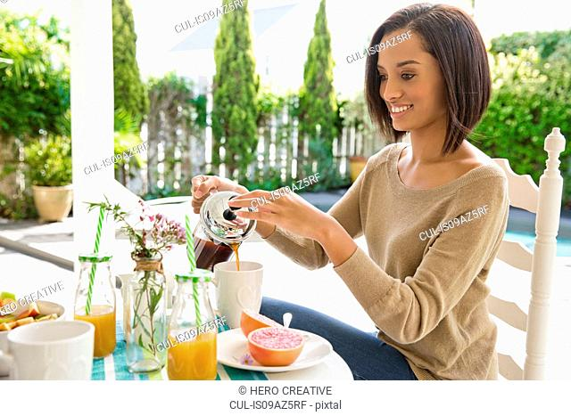 Young woman pouring coffee from french press