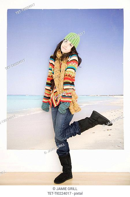 Woman in winter clothing in front of beach picture