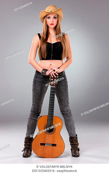 The beautiful girl in a cowboy's hat and acoustic guitar on a gray background