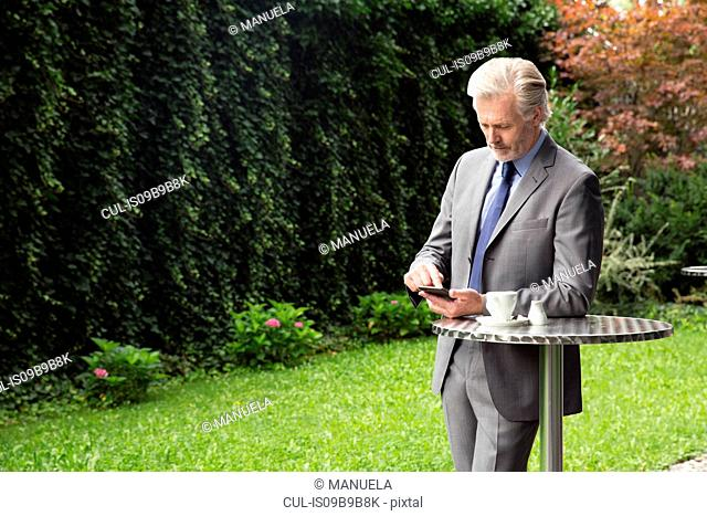 Businessman learning against cafe table texting
