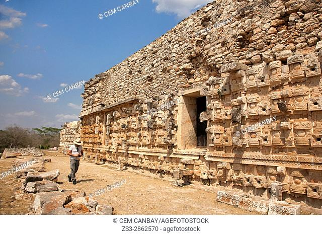 Tourist in front of the Palace Of Masks-El Palacio De Los Mascarones or Codz Poop in Maya Archaeological Site Kabah in the Puuc Route, Yucatan State, Mexico