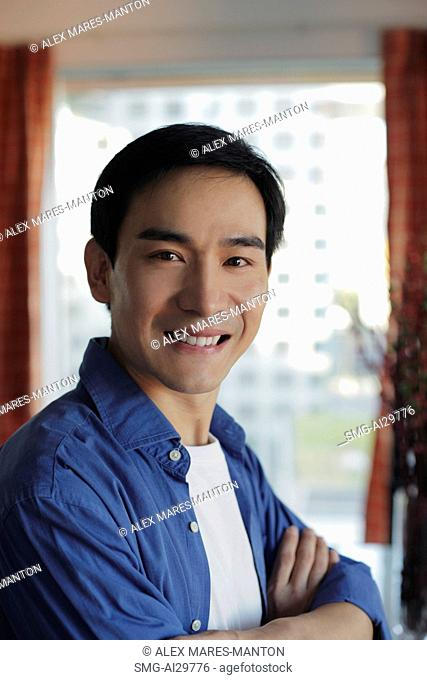 Head shot of man smiling in front of window