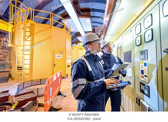 Workers checking data in generating hall in hydroelectric power station
