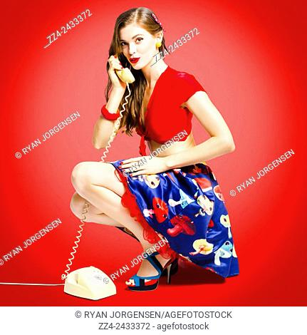 Full length portrait of a young pin-up woman in retro rockabilly style calling to buy clothes on old phone. Call connect