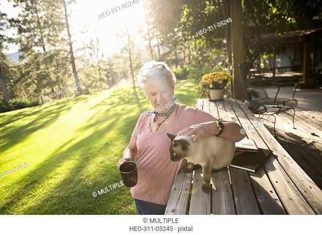 Senior woman petting cat and drinking coffee on sunny, idyllic patio