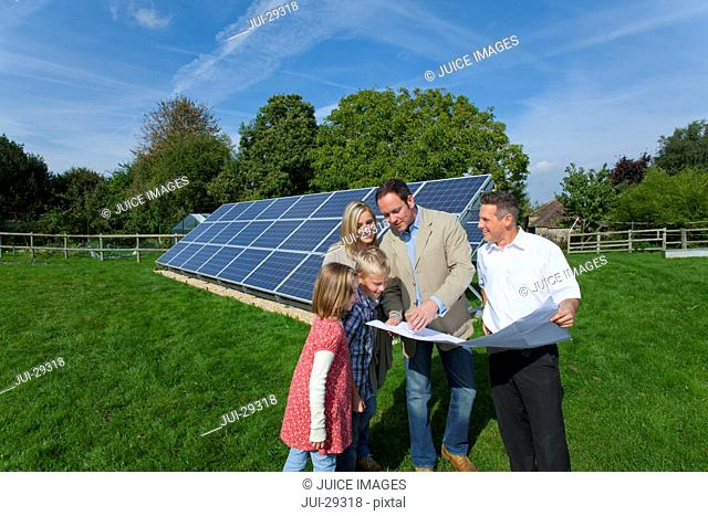 Technician holding blueprints talking to family near large solar panels