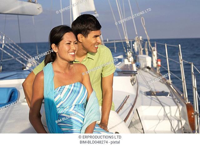 Multi-ethnic couple sitting on sailboat