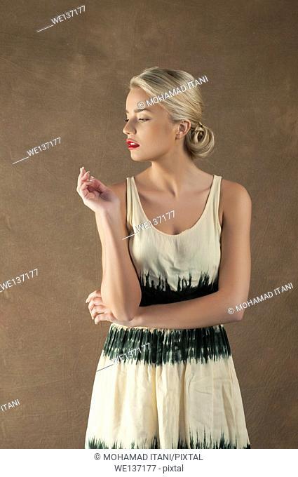 Beautiful young woman in yellow dress looking away