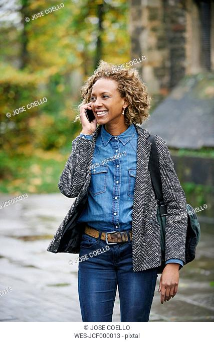 Portrait of smiling woman telephoning with smartphone