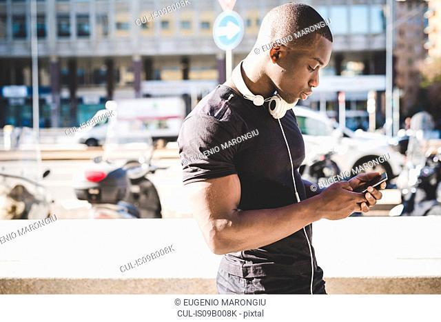 Young man outdoors, holding smartphone, headphones around neck