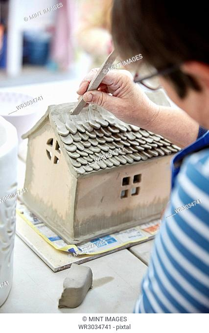 A woman potter using a small shaping tool to create the roof details for a clay model of a house
