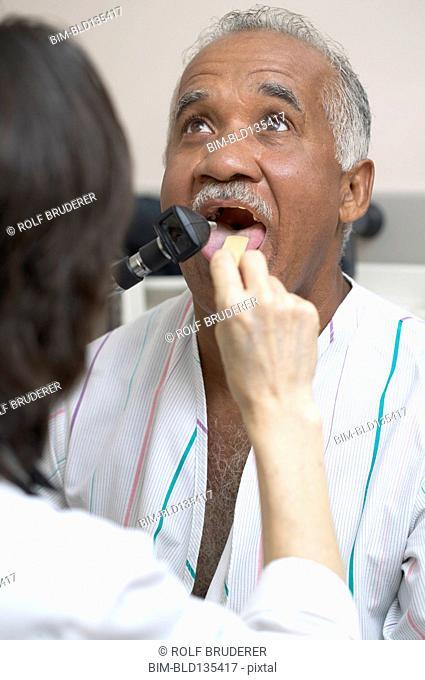 Doctor checking Senior man's tongue