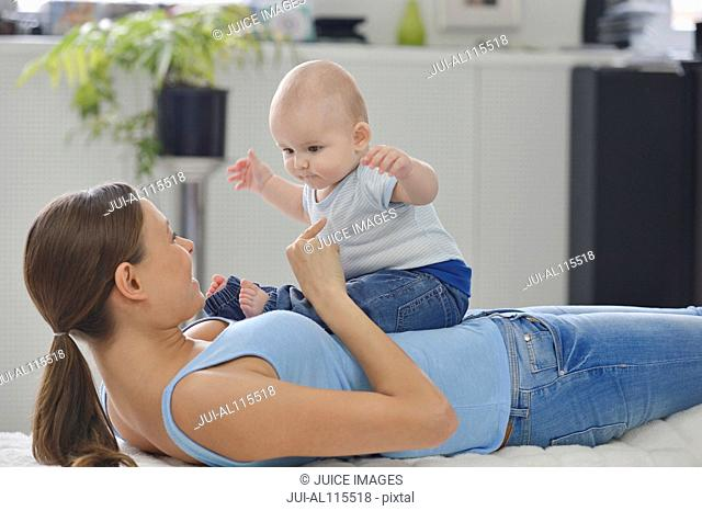Baby boy sitting on mother