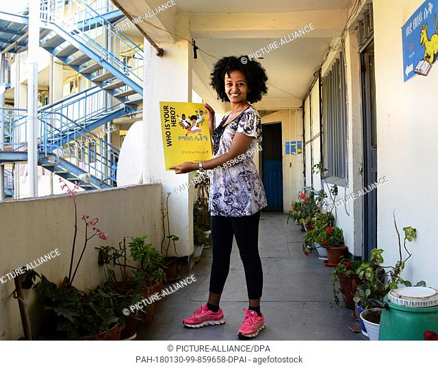 Bruktawit Tigabu, founder of the Whiz Kids Workshop media company, showing a small advertisement with her cartoon heroines in front of the offices of her...